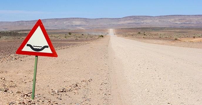 Flood warning sign along a gravel road, Namibia